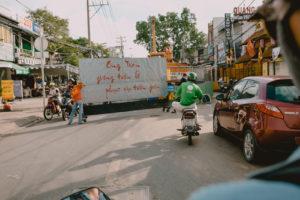 Two men move banner across street and block motorbike traffic. Taken on June 29.
